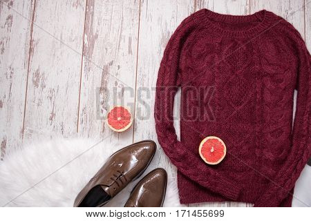 Maroon knitted sweater brown patent leather shoes cut grapefruit halves. Wooden background space for text. Fashion concept. top view