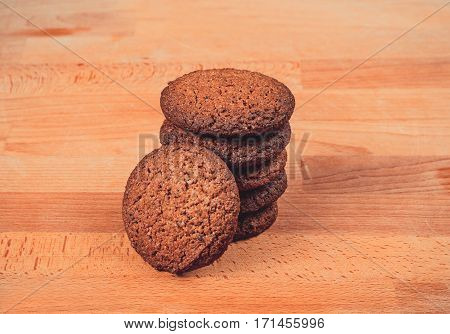 Homemade oat cookies on a wooden background. Oatmeal cookies on a old wooden cutting board. Freshly baked oatmeal raisin cookies on rustic wood table. Closeup from above with natural lighting.