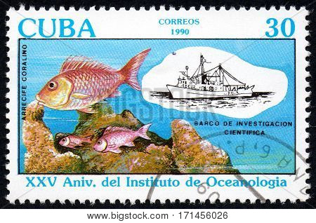 UKRAINE - CIRCA 2017: A stamp printed in Cuba shows Fish in a coral reef and a research vessel circa 1990
