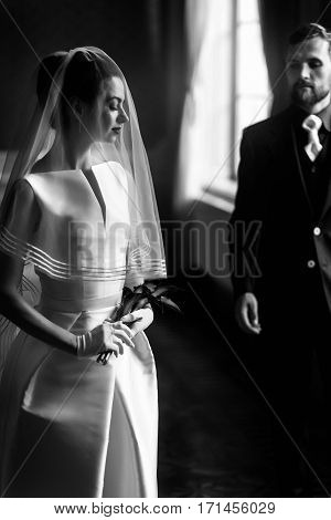 Elegant Gorgeous Bride Gently Looking Under Veil At Stylish Groom Standing At Window Light, Holding