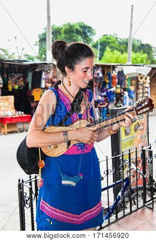 ANTIGUA,GUATEMALA -DEC 24, 2015: Young beautiful woman playing guitar in the street of Antigua on Dec 24, 2015. Guatemala.