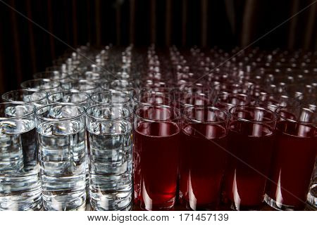 Glasses of water and red drink on blank black background