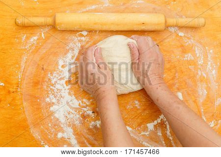 Photo of woman kneads dough on table with flour