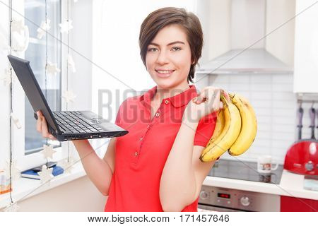 Girl with bananas and laptop stands in kitchen