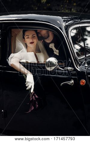 Luxury Elegant Wedding Couple Kissing In Stylish Black Car. Gorgeous Bride And Handsome Groom In Ret