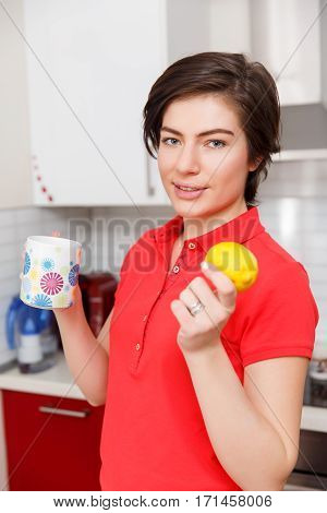 Brunette with lemon and cup in hand in kitchen