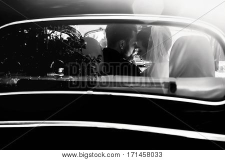 Luxury Elegant Wedding Couple Embracing In Stylish Black Car In Light. Unusual View From Back. Gorge