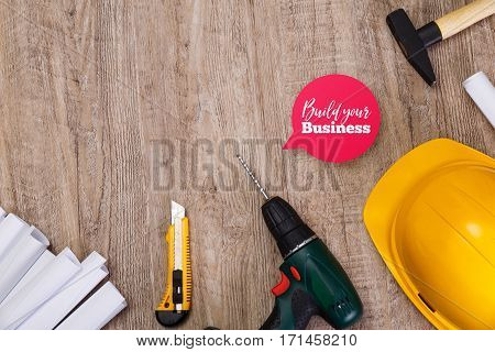 Hammer, helmet and drill. Paper knife. Build your business speech bubble. Architecture plans. Wood rustic background.