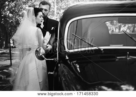 Luxury Elegant Wedding Couple Embracing At Stylish Black Car In Light. Gorgeous Bride And Handsome G