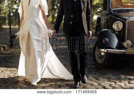 Luxury Elegant Wedding Couple Walking And Holding Hands Close Up At Stylish Black Car In Light In Pa