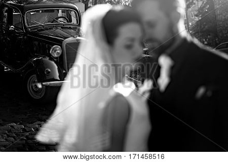 Gorgeous Elegant Bride And Stylish Groom Embracing, Gentle Touch In Light. Unusual Luxury Wedding In