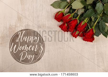 Red roses on wood vintage background. Happy womens day. Concept for romantic love design. Fresh natural flowers. Wooden grunge board.