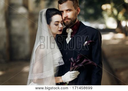 Elegant Gorgeous Bride And Stylish Handsome Groom In Sunlight Posing. Unusual Luxury Wedding In Retr