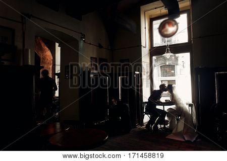 Luxury Wedding Couple Holding Hands And Kissing In Cafe In Morning Near Window In Soft Light. Elegan
