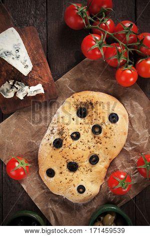 Italian pizza focaccia similar to pizza with black olive slices