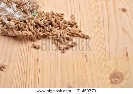 Wholemeal Pasta Fusilli From Organic Whole Grain Spelt Falling From A Bag On A Rustic Wooden Table.