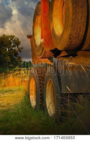 Old vintage Oregon log truck wheels with dramatic sky and lighting sitting in field.