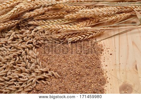 Picture Of Wholemeal Pasta From Organic Grain, Cereal Flour And Ears Of Wheat On A Rustic Wooden Tab