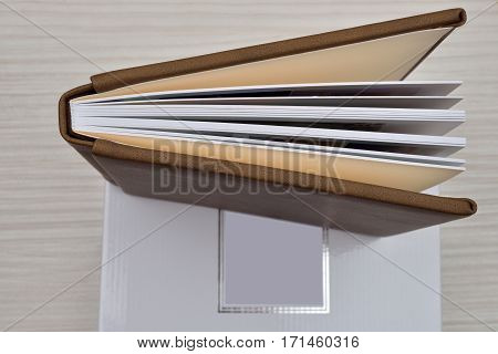 Top View Of Wedding, Christening  Brown Leather Photo Album Ajar And Storage Box On White Wooden Bac