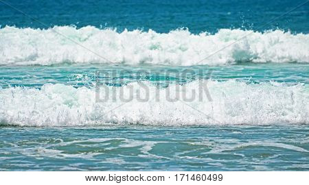 Turquoise green waves with foam on a sandy beach in Indonesia