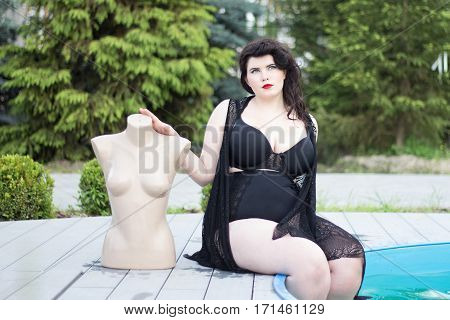 Young beautiful busty curvy plus size model with big breast in black bra professional makeup and hairstyle sitting near the outdoors pool
