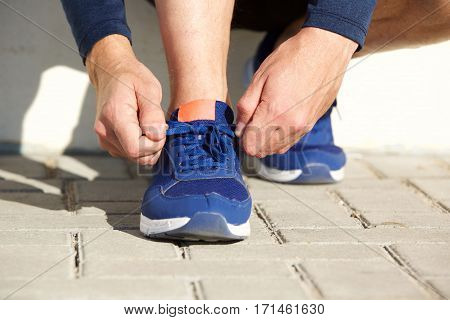 Sports man hands timing shoelaces before going on a. Run