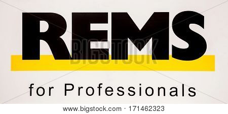 Moscow, Russia - February, 2016: Rems logo. Sticker black letters on the white wall. Rems products for processing pipes, in particular for the installation of sanitary and heating systems