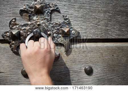 Man knocks on old door knocker on wooden door