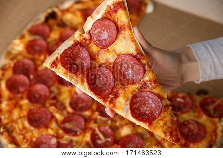 Hand holding a piece of pepperoni pizza. Hot homemade food. Sliced of fresh italian classic salami pizza. Popular topping with cheese. Baked meal.