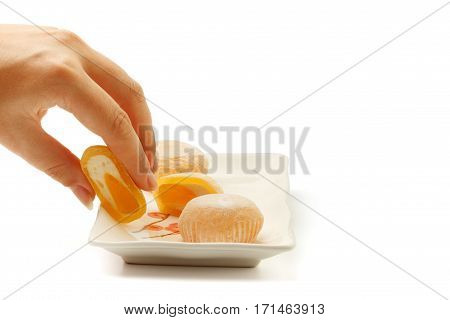 Beautiful elegant female hand taking mango mochi dessert from white square ceramic plate with japanese rice cakes isolated on white background.
