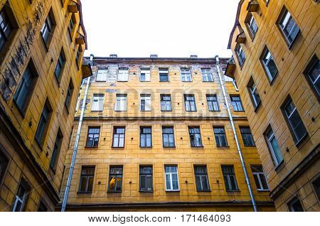 Old houses and narrow courtyards closed city of St. Petersburg, peeling walls and windows of houses