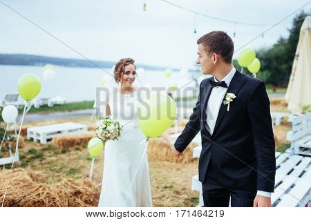 beautiful young wedding couple kissing , blonde bride with flower and her groom in summer park with sun haze