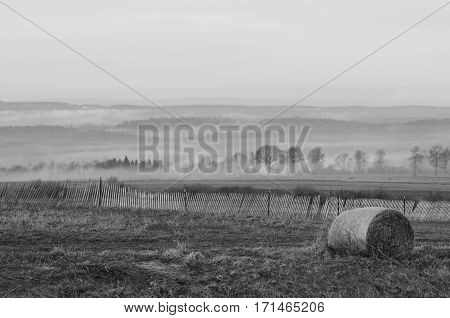 Black and white of one hay bale and the morning Fog on the hillside of upstate New York
