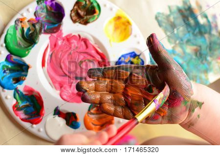 Child painting hand with a paintbrush and background with palette of colorful paint