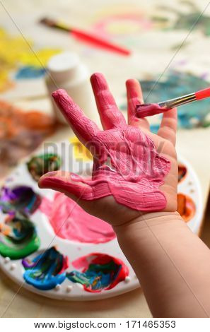 Child painting her hand with pink paint and background with palette of colorful paint