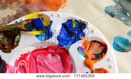 Mixed paint and paint covered paintbrush on a palette of colorful paint