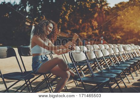 Curly brunette smiling beautiful girl on empty seat rows of folding chairs in park before concert making selfie on her digital tablet attractive young woman using her touch pad in park before event