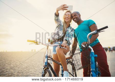 couple taking a break from riding bikes to take selfies shot with lens flare and warm tone