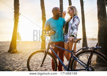 active couple taking time to relax after riding bikes on the beach at santa monica california