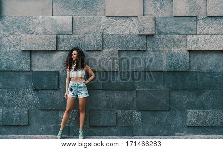 Attractive curly brunette hipster smiling girl in teal jeans shorts in front of street stoned patterned wall background with copy space for your advertising text message or promotional content