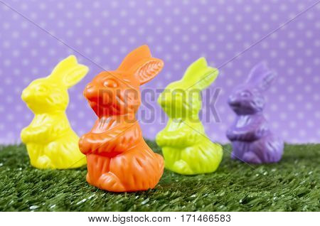 Lots of colorful Easter bunnies on the artificial grass.