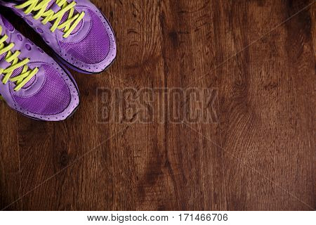 Fitness gym equipment. Purple sneakers. Workout footwear. Sport trainers on grunge rustic wood background.
