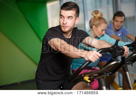 Sports people on exercise bikes in top form in gym