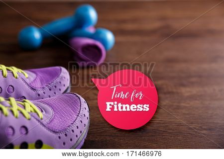 Fitness gym equipment. Sneakers, dumbbells with towel. Time for fitness speech bubble. Workout footwear. Grunge rustic wood background.