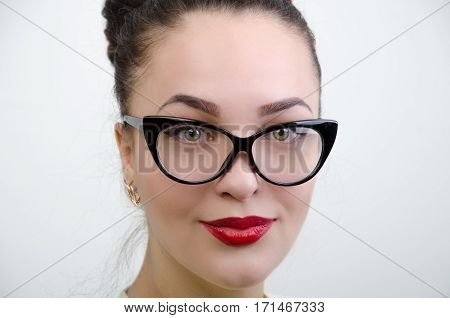 face of a young woman in glasses on white background