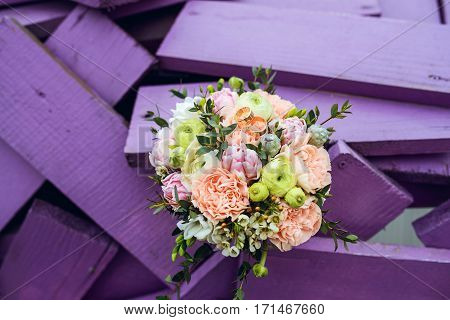 beautiful weding bouquet with rings on purple wooden background