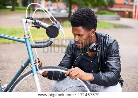 a young man checking his bicycle wheel