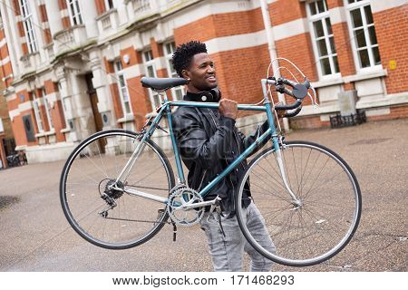 a happy young man carrying his bike