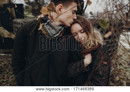 Stylish Hipster Couple Hugging Gently In Autumn Park. Fashionable Man And Woman Showing True Feeling