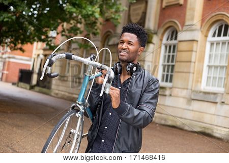 young man carrying his bike in the street